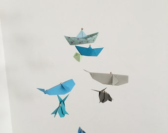 Origami mobile 'Song of the whales' with whales and boats.