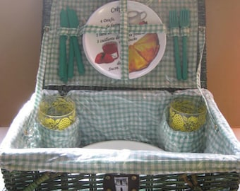 Vintage green wicker fully stocked picnic basket.
