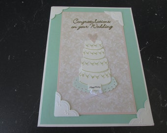 """Wedding Congratulations Card, Features the beautiful 4 tier cake with a pink heart on the top, """"Happy Wedding"""","""
