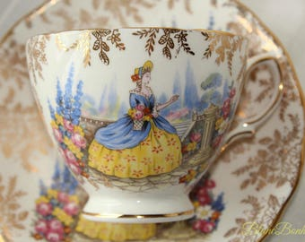 Colclough, England: tea cup and saucer, white, gold, yellow and blue, with a elegant lady in crinoline