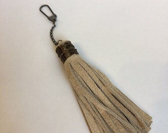Large beige suede tassel keychain with antique copper finishing.