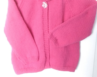 Katie - rose pink, hand knitted, long sleeved, girls round neck cardigan with cabled collar and ribbon button fastening. Age 4 - 5 years.