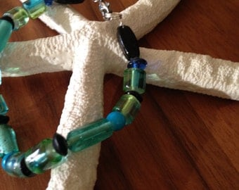 Beaded bracelet in modern colors-blues, greens and black, silver colored, beads