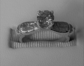 One carat Moissanite set in Sterling Silver.  Textured Neoclassical design suitable to be used as engagement ring.