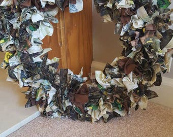 Wreath that hangs on a door. The colors are green, camo, and brown