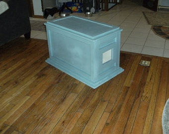 A toy chest converted into a kitty litter box.