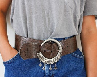 Vintage faux snakeskin wide belt with crescent moon silver buckle with charms. Fits size small 27-30 1/2 in. waist/hips. Missing two charms.