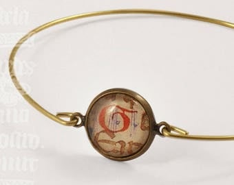 """Orbis"" - manuscript under glass bracelet"