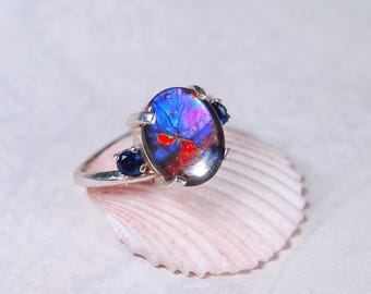 Ammolite ring--For those that search for the very rare and unusual in ammolite.Rare pink,purple and blues with natural sapphire companions.