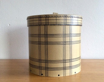 Vintage hat box or storage box in natural colored cardboard with dark blue chequered decoration