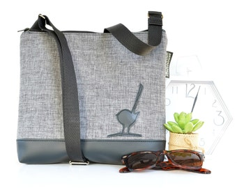 Womans handmade crossbody bag  Grey front with black vegan vinyl base and back. Black bird detail.