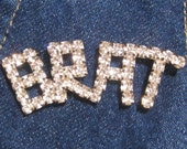 """Rhinestone BRAT pin in Capital Letters. Clear Bright Rhinestones form the word BRAT.   2.5"""" W.  Great on Denim or Velvet.  1970's or 1980's"""