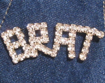 "Rhinestone BRAT pin in Capital Letters. Clear Bright Rhinestones form the word BRAT.   2.5"" W.  Great on Denim or Velvet.  1970's or 1980's"