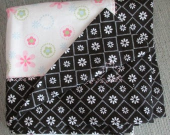 Soft flannel baby self binding receiving blanket with pink flowers on top and black with white flowers