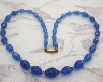 A lovely vintage jewelry necklace made with graduated oval sparkly rich blue faceted crystal beads with blue sapcers