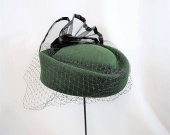 Vintage 1980s green wool pillbox with black veiling and large mesh and satin rosette detailing