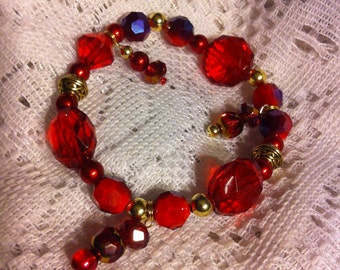 Red glass and acrylic mix beaded bracelet with antique gold plated Celtic knot beads.