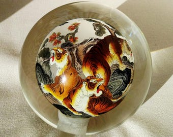 Ball of glass blown with interior paint by hand depicting scene from several different colors Tigers