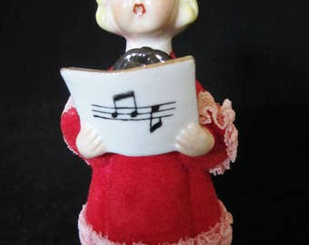 50's Girl Caroler Figurine- in red-flocked choir robe trimmed in white lace. She is holding a Christmas song book. Adorable facial features!