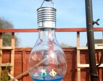 Plastic solar powered lightbulb with resin encased scene.