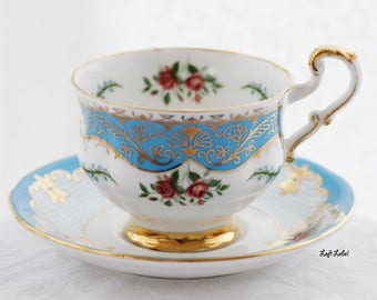"""Paragon by appointment aquablue teacup and saucer, """"Burghley K"""".-pattern luxuriously covered in gold paint, warranted, marked, England"""