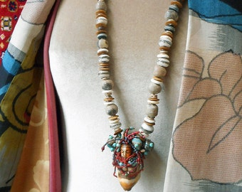 Precious, Primal Venus amulet necklace, carved antler, fossilized dinosaur bone