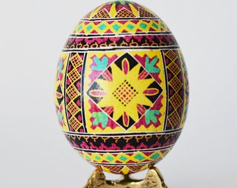 Ukrainian Easter egg pysanka in traditional patterns yellow turquoise red