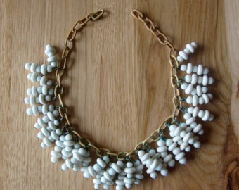 Very vintage white glass beads wired to celluloid chain in very beautiful vintage condition and ready for your summer wardrobe .