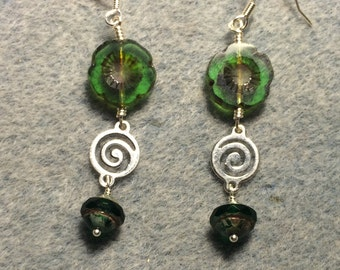 Emerald green Czech glass pansy bead dangle earrings adorned with silver swirly connectors and emerald green Czech glass Saturn beads.