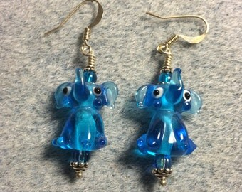 Translucent turquoise blue lampwork sitting elephant bead earrings adorned with turquoise Czech glass beads.