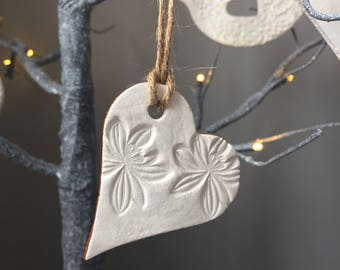 Small white & metallic bronze clay hanging heart, with embossed flower decoration