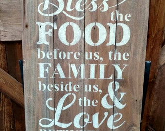 Bless the food before us, the family beside us and the love between us. Pallet sign, rustic brown boards with antique white lettering.