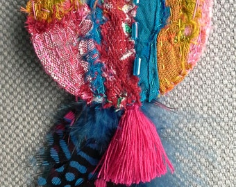 Textile brooch, bohemian spirit, ethnic style, muddle of well-matched colors.