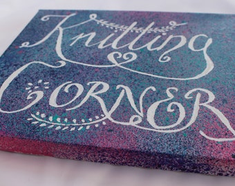 """Knitting Corner Canvas for your creative space.  White hand lettering on Blue/Purple, green and pink splattered background 10"""" x 8"""""""