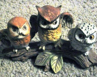 Three ceramic statue, figurine owls on a branch