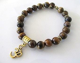 Tiger eye bracelet gemstone bracelet om charm yoga bracelet solar plexus chakra bracelet boho bracelet new age meditation bracelet healing.