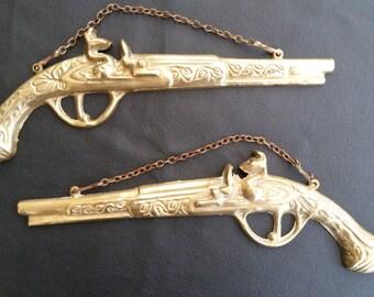 Pair of wall mounting brass coloured flintlock pistols