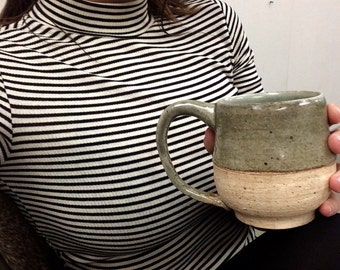 Green celadon mug with exposed claybody and four finger handle