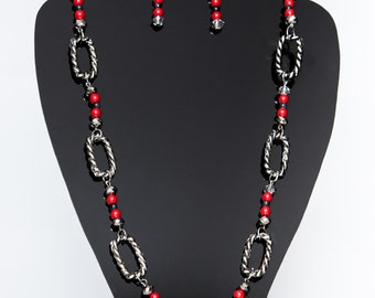 Red, grey and silver beaded necklace with metallic accessories.