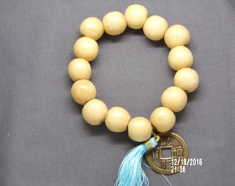 B1285 Medium Size Cream Colored Wooden Beaded Bracelet with Chinese Good Luck Charm and Tassel.