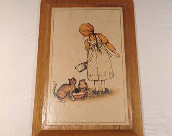 """Framework """"Hobby Hollie"""" - card mounted on plate of mahogany - little girl with cat - Carlton Cards Limited 1976 / / made in the Canada"""