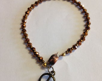 Brown crystal bracelet with peace sign charm