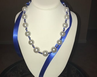 The FCM.   Glass pearl necklace with royal blue and white ribbons for the ties.
