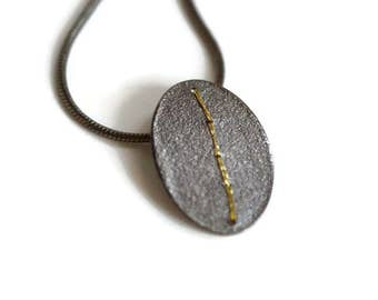 Oxidised Silver oval disc pendant stitched with gold embroidery thread
