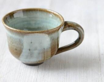 A Wheel Thrown Black Mountain Stoneware Clay Coffee cup or mug with porcelain slip decor