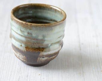 A Wheel Thrown Black Mountain Stoneware Clay tumbler with porcelain slip decor