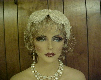 Beige fascinator hat with back bow and face veil without tears