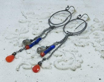 Cluster of colourful stones dangling from silver chains.  Coral, lapis lazuli, labradorite, carnelian