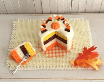 Miniature Halloween Cake With a Pumpkin and Candy Corn On Top and a Slice of Cake