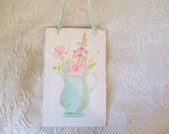 a turquoise pitcher filled with flowers handpainted on bookboard